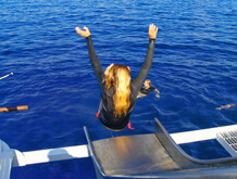 blonde girl slides into the tropical blue maui ocean with arms outstretched