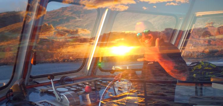 captain on sunset cruise smiling